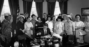AAUW members Minnie Miles (front row, fourth from right) and Reps. Edith Green (left of president, in white suit), Martha Griffiths (second from right), and Julia Hansen (far right) with President John F. Kennedy as he signs the Equal Pay Act into law on June 10, 1963. CREDIT: Abbie Rowe, White House Photographs. Courtesy of John F. Kennedy Presidential Library and Museum, Boston